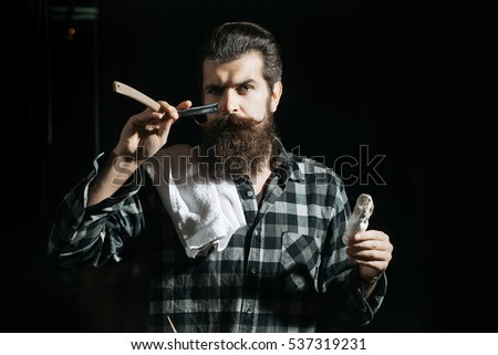 Handsome man, bearded hipster, brunette with long beard and moustache shaves with open vintage razor with blade and shaving brush on dark background