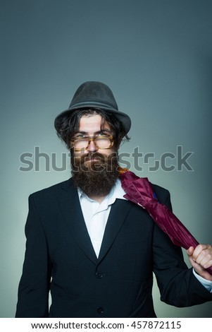 Handsome man bearded hipster male wears vintage hat glasses black suit with umbrella cane on grey wall