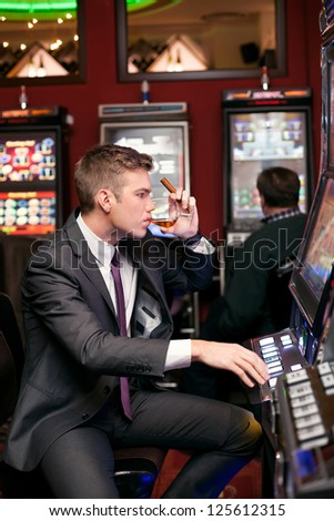 handsome man being concentrated in playing the slot machine - stock photo