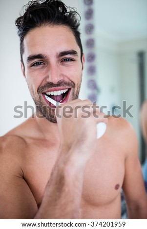 Handsome man brushing his teeth in bathroom - stock photo