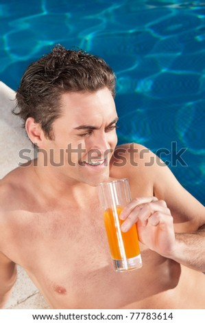 Handsome man by the poolside with a glass of orange juice - stock photo