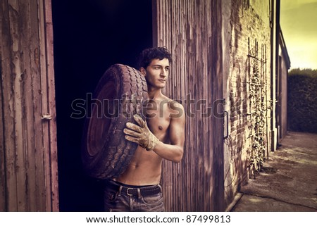 Handsome man carrying a car tire