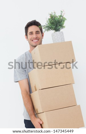 Handsome man carrying boxes because he is moving - stock photo