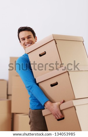 Handsome man carrying stack of boxes - stock photo