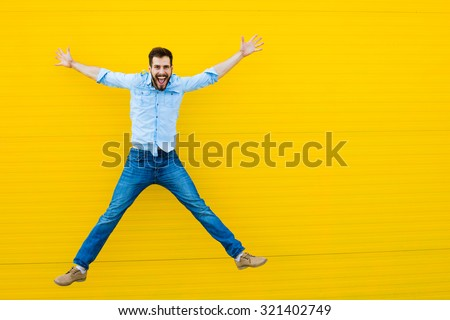 handsome man casual dressed celebrating and jumping on yellow background