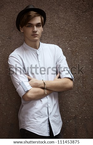 Handsome man casually leaning against the wall - stock photo
