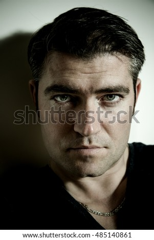 Handsome man close up portrait. Strong contrast, dramatic light