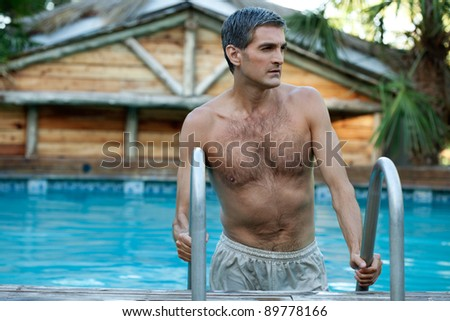 Handsome man coming out of the swimming pool and looking away