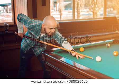 Handsome man concentrating on the game on the pool table. American pool billiard. Pool billiard game. Billiard sport concept. - stock photo