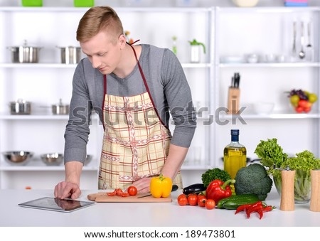 Handsome man cooking at home preparing salad in kitchen. - stock photo