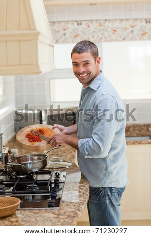 Handsome man cooking in the kitchen at home