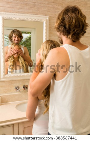 Handsome man covering his girlfriend eyes in the bathroom