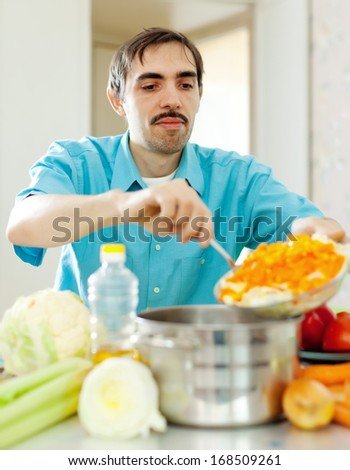 handsome man does lunch wit vegetables at kitchen - stock photo