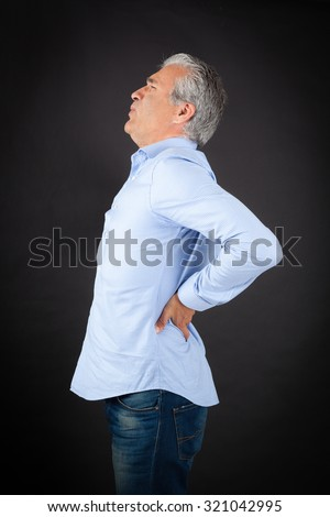 Handsome man doing different expressions in different sets of clothes: backache - stock photo