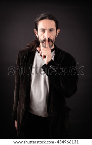 Handsome man doing different expressions in different sets of clothes: be quiet - stock photo