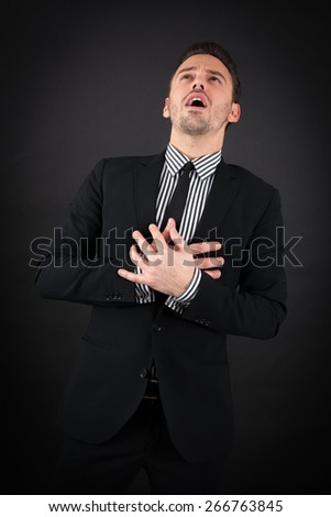 handsome man doing different expressions in different sets of clothes: heart attack - stock photo