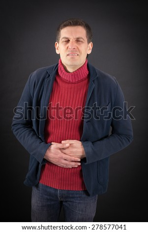 Handsome man doing different expressions in different sets of clothes: stomachache - stock photo