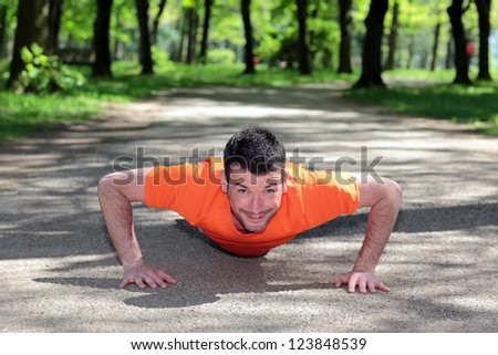 handsome man doing exercises in a park - stock photo