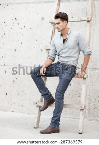 Handsome man dressed in a blue jeans shirt, jeans and a cap, posing