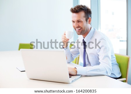 Handsome man drinking coffee in office while typing on laptop - stock photo