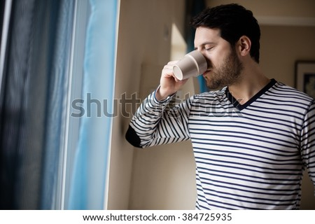 handsome man drinking coffee next to a window inside the house