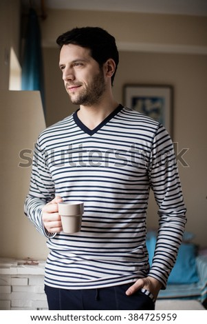 handsome man drinking coffee next to a window inside the house - stock photo