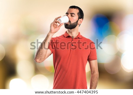 Handsome man drinking coffee on unfocused background