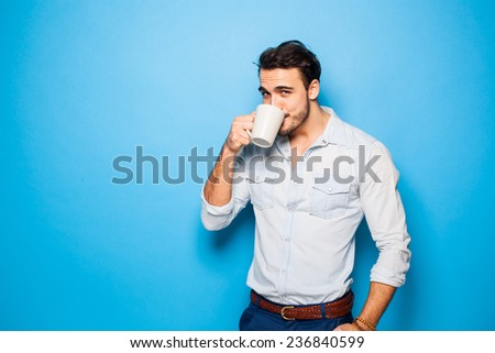 handsome man drinking coffee/tea on blue background - stock photo