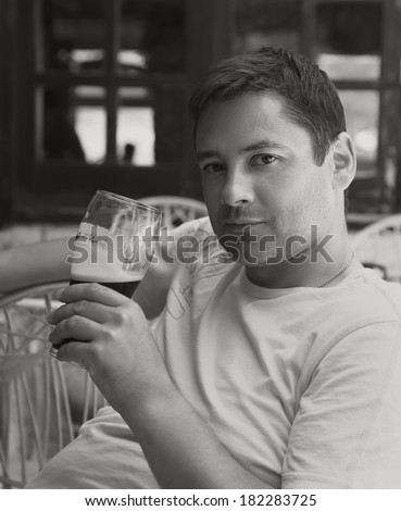 Handsome man drinking dark beer in pab. Black and white portrait - stock photo