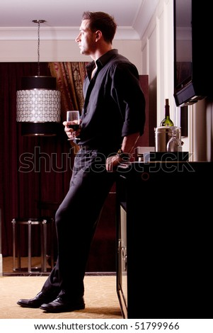Handsome man drinking red wine - stock photo