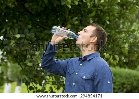 Handsome man drinking water in summer park - stock photo