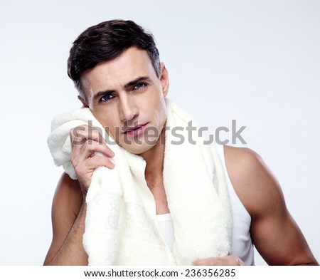 Handsome man drying his face with towel - stock photo