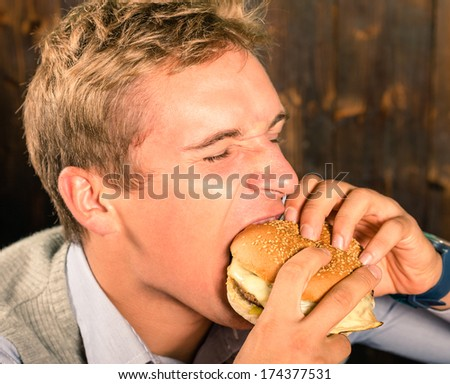 Handsome Man eating a Cheeseburger - stock photo