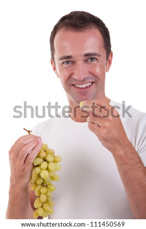 handsome man eating a green grapes, isolated on white background. Studio shot.