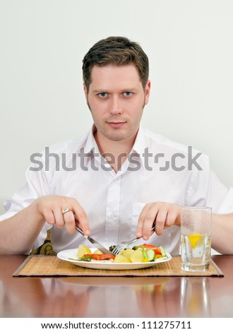 Handsome man eating with fork and knife - stock photo