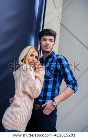 Handsome man embracing a sexy blonde woman and looking away - stock photo
