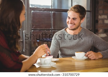 Handsome man enjoying cake and coffee with friend at coffee shop - stock photo