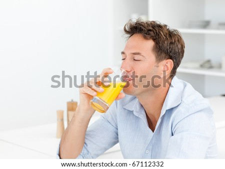 Handsome man enjoying his orange juice sitting in the kitchen at home - stock photo