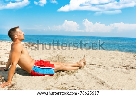 handsome man enjoying in sun on the beach - stock photo