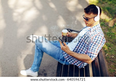 Handsome man enjoying music via digital tablet and headphones on a sunny day in the park