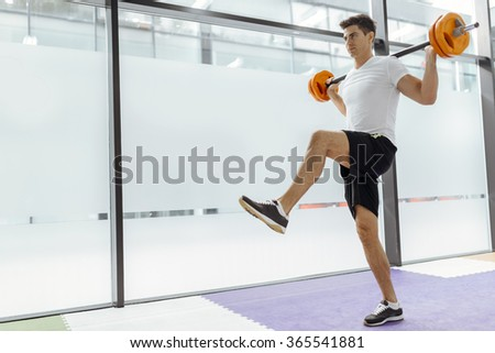 Handsome man exercising and lifting weights in fitness club - stock photo