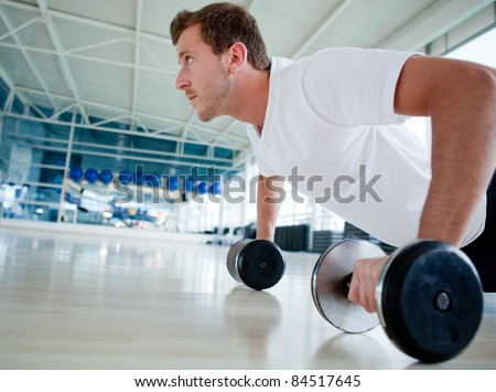 Handsome man exercising at the gym doing push ups - stock photo
