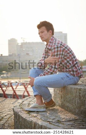 Handsome man, fashion model, with toupee sitting on stone stairs in summertime over city background - stock photo