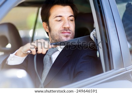 Handsome man fastening safety belt - stock photo