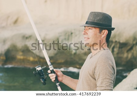 Handsome man fishing during his day off, selective focus