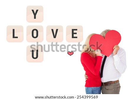 Handsome man getting a heart card form wife against love you tiles - stock photo