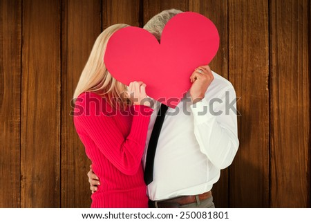 Handsome man getting a heart card form wife against wooden planks - stock photo