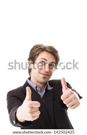Handsome man giving a thumbs up gesture of success, agreement and approval while looking upwards with a playful look isolated on white