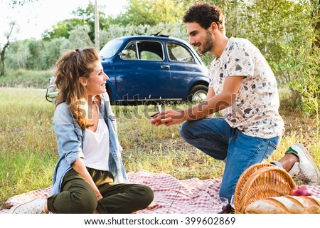Handsome Man Giving Engagement Ring To A Beautiful Young Woman - stock photo