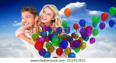 Handsome man giving piggy back to his girlfriend against bright blue sky with clouds - stock photo
